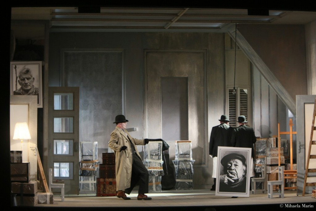 """The new tenant (Francisco Alfonsin) with his furniture removers and with photos of his """"ancestors."""" Set and light design by Helmut Stürmer. Photo by Michaela Marin"""