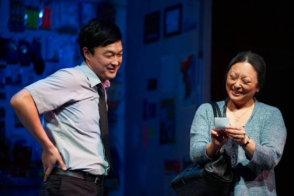 Dale Yim as Jung, the son, with his mother (Jane Luk) looking at a photo of Jung's young son (her grandson). Photo by Cylla von Tiedemann.