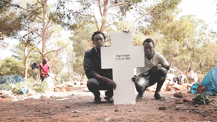 Picture of two refugees holding a memorial that was stolen by Centre for Political Beauty.