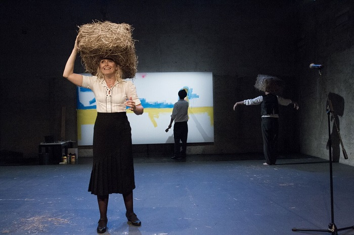 The painting, the actors—with Lucie Trmíková in the foreground, the hay from home eternal, and the microphone stand in Double Home.