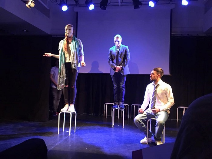 One of the court scenes where Tariq is questionned by Home Office representatives, played on stage by Kate Duffy in a mask with recorded voice. Photo credit: Phosphoros Theatre