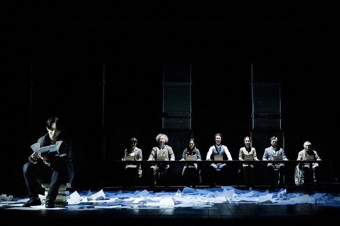 Konstantin (Gi-soo Gim) lisant son texte tandis que les autres jouent au loto. Photo: Jang Sung-yong