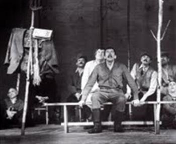 Chaque acteur entre avec « son bouleau » qu'il plante au sol. Sur un troc plus court que les autres, une pancarte en bois ou le nom du village est écrit à la main. Y sont disposés les vêtements de Kouzkine et la revue Novy Mir © Bajenov.