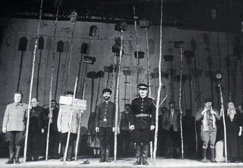Le Vivant d'après Boris Mojaev, mise en scène de Boris Liobimov. Sur la partie droite de la photo : Kouzkine (Valéri Zototoukhine), Dounia (Zinaïda Slavina) et leur cinq enfants. Les habitants du kolkhoze et les fonctionnaires se tiennent près des bouleaux. La « maison » de Kouzkine, est suggérée par un bouleau surmonté d'une pendule à coucou © Viktor Bajenov.