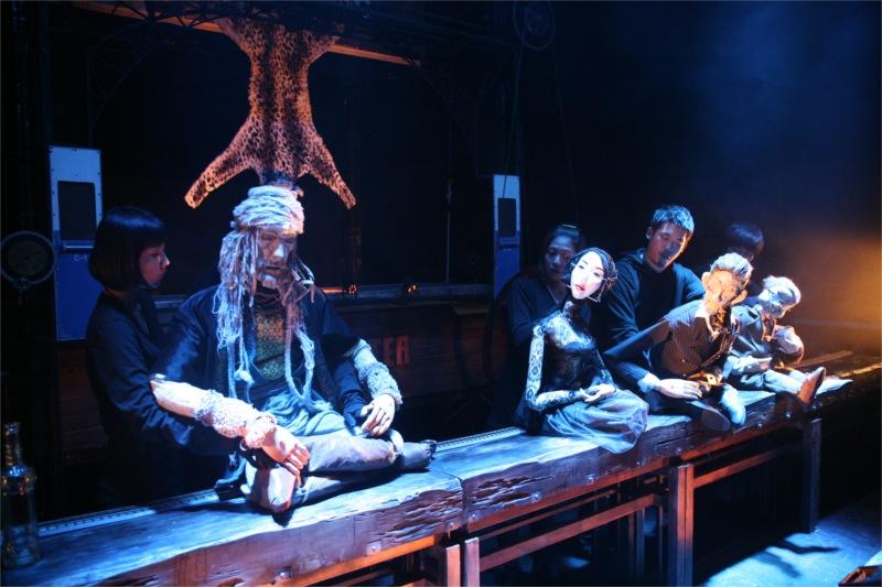 Changement d'échelle : les pantins sont des figures à dimension humaine. Le sculpteur les a fabriqués pour signifier d'entrée la différence de leur identité. Mamaï, guerrier sauvage, Touareg, montagnard, aventurier et poète, fait l'admiration des trois Coréens 'occidentalisés'. Nous voici dans le monde rugueux comme le bois, fruste, archaïque du vieux sauvage, un monde sur lequel pèse le lourd héritage de la tribu. La peau de léopard au-dessus de sa tête est autant une dépouille qu'une menace.