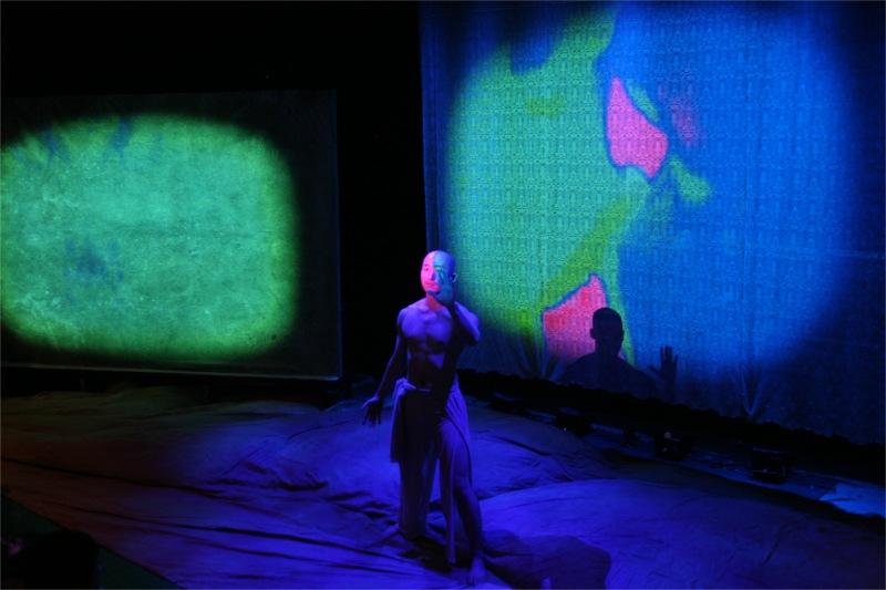 Le danseur au torse nu, au crâne rasé, baigne dans un espace de couleurs bariolées et de formes abstraites. D'où vient ce corps ? Dans l'univers minéral et archaïque des marionnettes, cette chair humaine nous paraît presque incongrue et irréelle. Elle nous semble artificielle, à l'image de ce visage divisé par les hasards des projections ou de l'ombre qui s'inscrit sur la toile. Grâce à lui, nous avons un instant retrouvé notre corps, mais nous regrettons déjà le monde des pantins, des images, des corps irréels.
