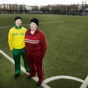 Kirsi Asikainen (left) and Marja Myllylä as male maintenance workers of a sports field in a publicity photo for Field. © Kirsi Tuura
