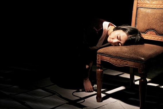 La joue posée sur un siège à l'épaisse peau de cuir, Na Hyeseok cherche-t-elle la protection d'une âme compatissante ou aimante ? Qui la lui fournirait ? Le fauteuil est le seul objet vivant et chaleureux de cette scénographie. Dans l'espace vide et technologique, dans l'univers abstrait de ces feuillets détachés, ce siège donne une impression de stabilité et de confort. La main qui tient le micro repose délicatement sur le sol, comme si la plainte et la souffrance restaient en suspens pendant un court instant.