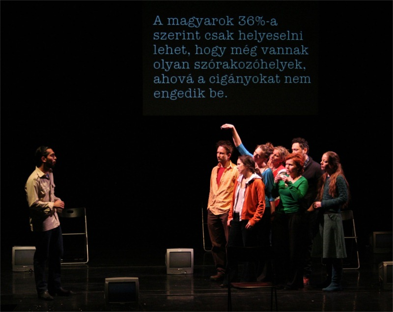 "Scene from PanoDrama's ""Word for Word"" (dir. Anna Lengyel). © Margó Klecsán. (Translation of the text behind the actors: ""36 percent of Hungarians find one can only approve of clubs which don't allow Gypsies in."")"