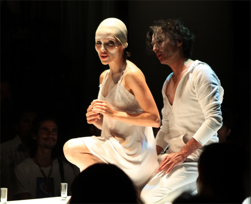 Camila Rocha and Diego Aramburo as Juliet and Romeo perform on a table with the spectators sitting around it in three rows.